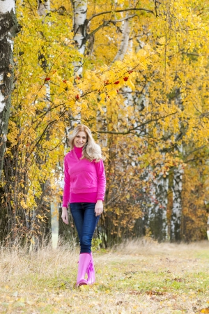 woman wearing rubber boots in autumnal nature photo