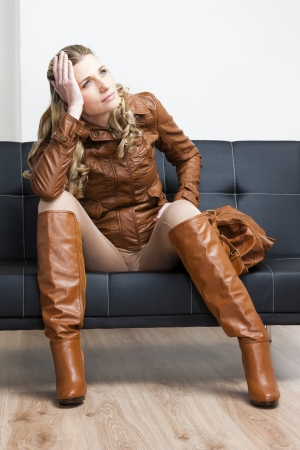 woman wearing brown jacket and boots sitting on sofa photo