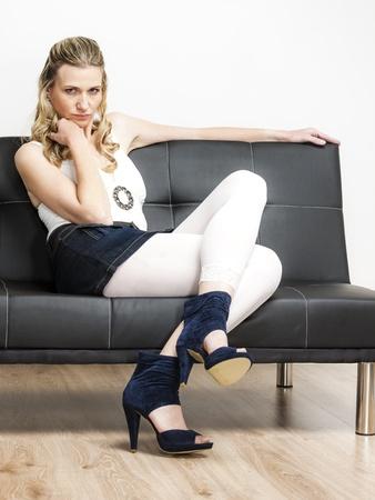 femme portant des chaussures d'été assis sur le canapé