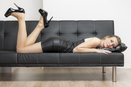 woman wearing black dress and pumps lying on sofa photo