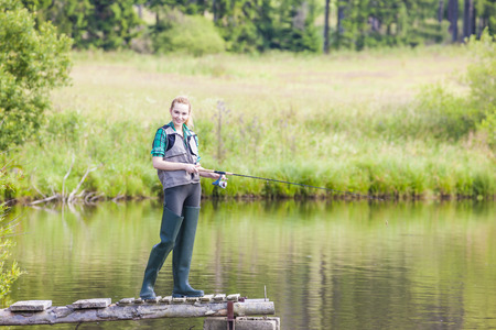 fisherwoman: young woman fishing on pier at pond