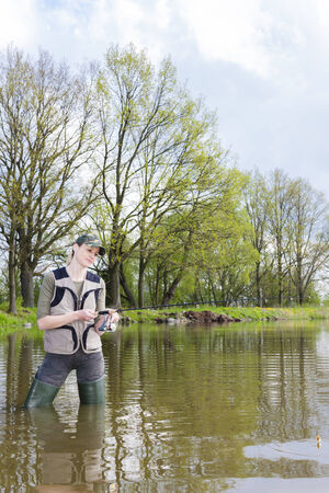 woman fishing in pond in spring photo