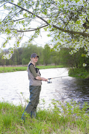 fisherwoman: woman fishing by the river in spring