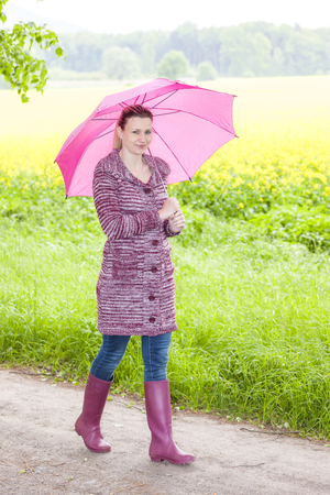woman wearing rubber boots with umbrella in spring nature photo