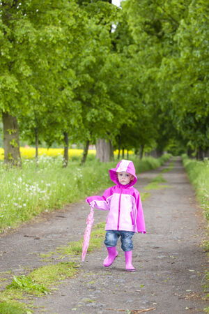little girl wearing rubber boots with ubrella in spring alley photo