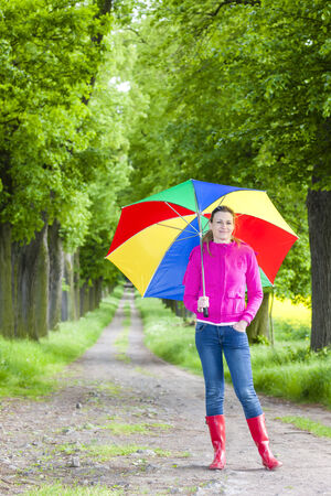woman wearing rubber boots with umbrella in spring alley photo
