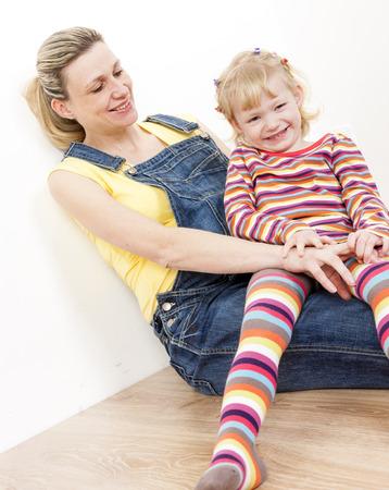 pantimedias: niña con su madre embarazada sentada en el suelo