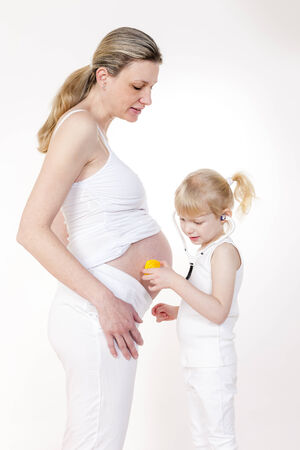 caretaking: little girl caring after her pregnant mother Stock Photo