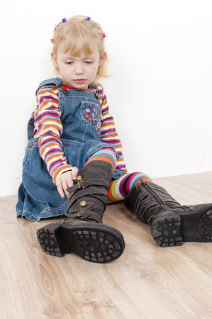 little girl putting on boots photo