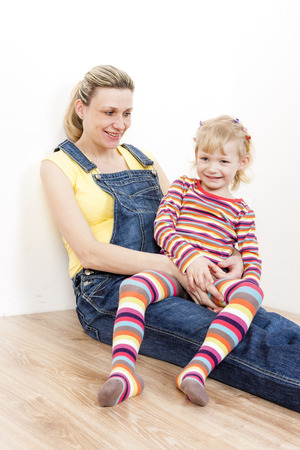 pregnant jeans: little girl with her pregnant mother sitting on floor