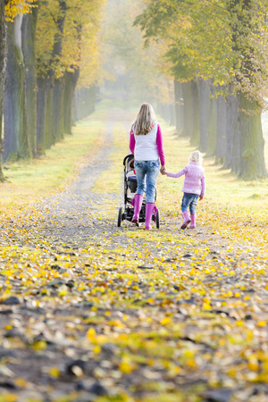 mother and her daughter with a pram on walk in autumnal alley photo