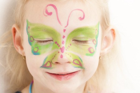 adorning: portrait of little girl with face painting