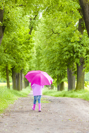 rubber boots: little girl wearing rubber boots with umbrella in spring alley Stock Photo