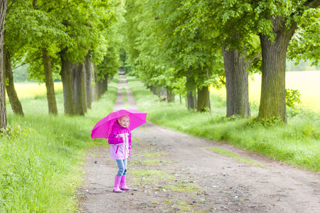 rubber boots: little girl wearing rubber boots with ubrella in spring alley Stock Photo