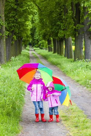 rubber boots: little girls wearing rubber boots with umbrellas in spring alley