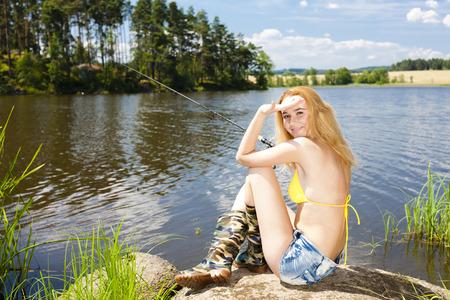 jonge vrouw vissen in de vijver in de zomer