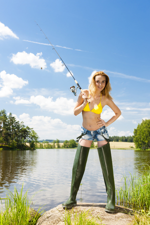 fisherwoman: young woman fishing at pond in summer
