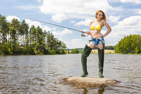 fisherwoman: young woman fishing in pond during summer