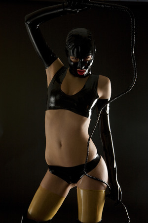 dominant: woman wearing latex clothes with whip Stock Photo