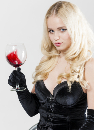 degustation: portrait of young woman with a glass of red wine