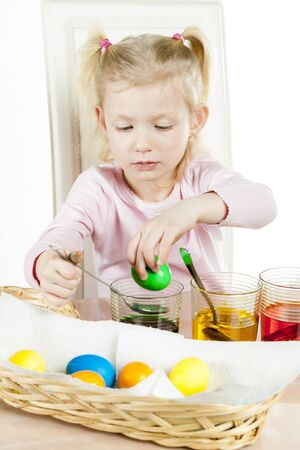 creative egg painting: portrait of little girl during Easter eggs coloration