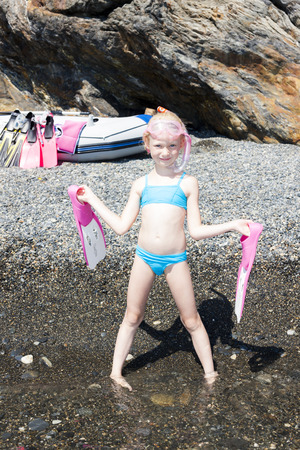 swim mask: little girl on the beach at sea ready for snorkeling Stock Photo