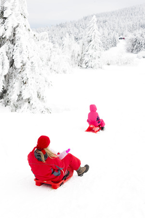 mother and her little daughters with bobs in snow photo