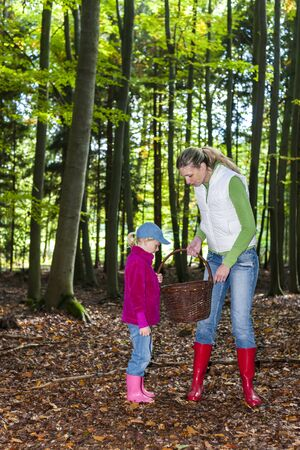 mother with her daughter doing mushroom picking photo