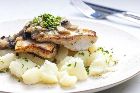 pikeperch: pikeperch on butter with mushroom sauce and spring potatoes Stock Photo