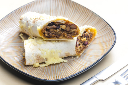 close up food: burrito filled with beef minced meat and beans baked with gouda cheese