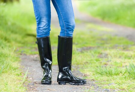 detail of standing woman wearing rubber boots Stock Photo