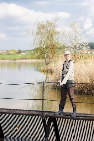 fisherwoman: woman fishing on pier at pond Stock Photo