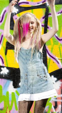 graffito: young woman standing at graffitti wall Stock Photo