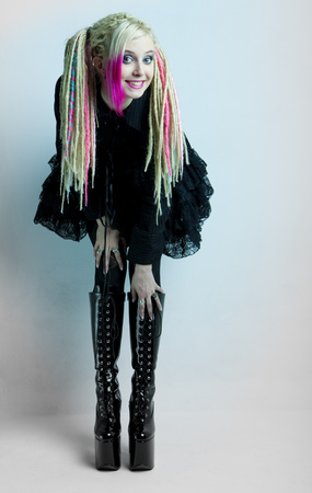 young woman with dreadlocks wearing extravagant clothes and boots photo