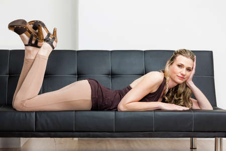 summer shoes: woman wearing summer shoes lying on sofa