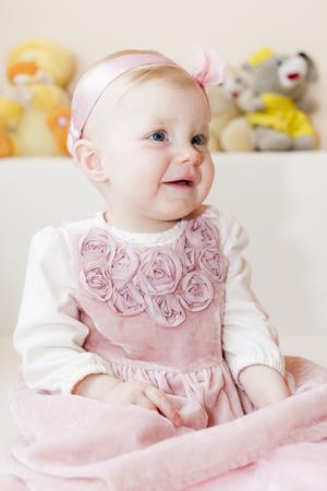 infantile: portrait of sitting toddler girl wearing pink dress