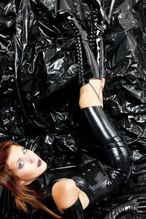 lying woman wearing latex clothes photo