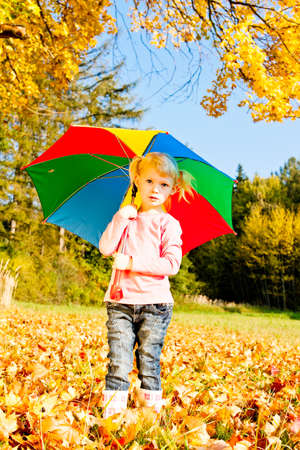 wellingtons: little girl with umbrella in autumnal nature