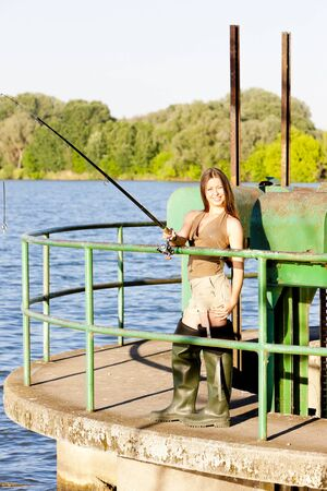 fisherwoman: young woman fishing at pond