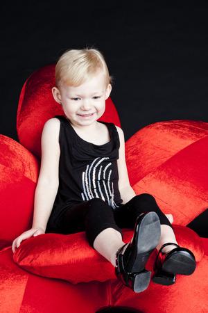 little girl sitting: little girl sitting on red armchair