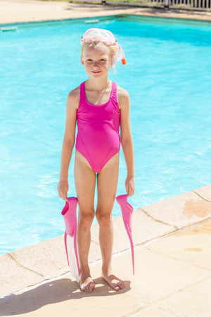diving pool: little girl with snorkeling equipment at swimming pool Stock Photo