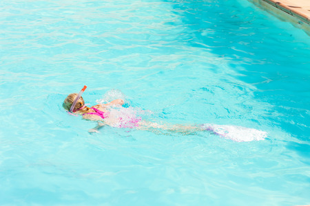 little girl swimsuit: little girl snorkeling in swimming pool Stock Photo