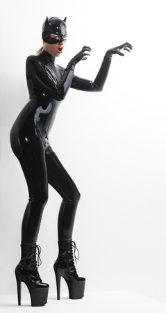 extravagance: standing woman wearing latex clothes