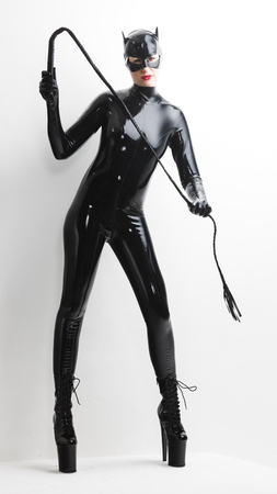 dominant woman: standing woman wearing latex clothes with a whip