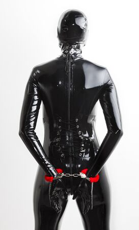 fetishism: woman wearing latex clothes with handcuffs Stock Photo