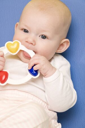 6 12 months: portrait of baby girl with a rattle toy