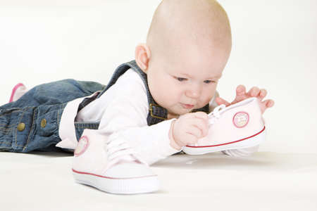 6 12 months: lying down baby girl holding shoes