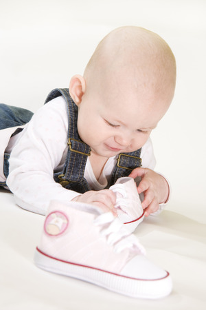 6 12 months: portrait of lying down baby girl holding shoes Stock Photo