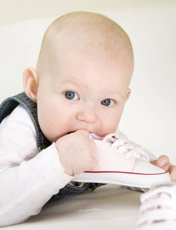 defenceless: portrait of lying down baby girl holding a shoe