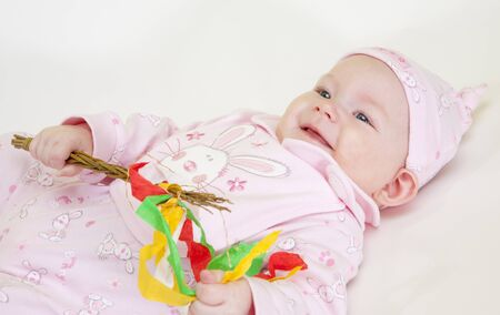 0 6 months: portrait of lying down baby girl holding a willow stick (Czech Easter)